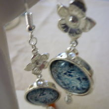 Beautiful sterling silver earrings set with vintage blue flower cabochons and five petal flowers.