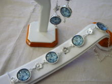 Beautiful handmade bracelet and earring set made from sterling silver inlaid with vintage blue flower cabochons and silver flowers.